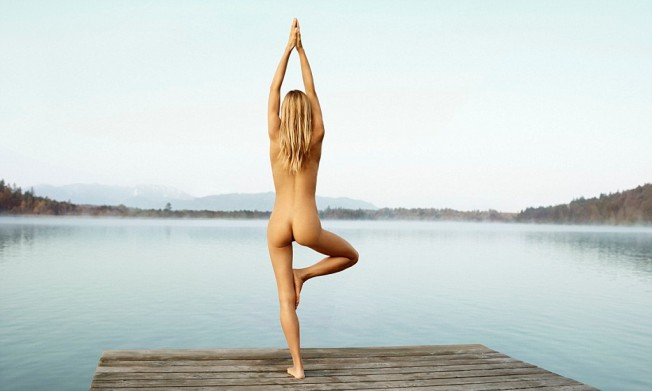 Young naked woman standing yoga pose on wooden pier --- Image by © Stefan Hauck/Corbis
