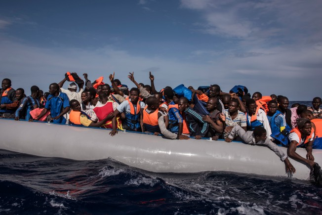 Italian sailors with the Uraniam Navy Ship rescue 109 African migrants from Gambia, Mali, Senegal, Ivory Coast, Guinea, and Nigeria, from a rubber boat in the sea between Italy and Libya, October 4, 2014. The migrants claimed to have left from Tripoli the evening of October 3rd, and spent the night moving north. The Italian Navy has several navy ships patrolling international and Italian waters at any given time in an attempt to rescue migrants, and transfer them safely to shore in Italy. Since the beginning of 2014, roughly 120,000 refugees have landed in Italy, more than double the total for the entire year of 2013. (Credit: Lynsey Addario for The New York Times) NYTCREDIT: Lynsey Addario for The New York Times NYTCREDIT: Lynsey Addario for The New York Times