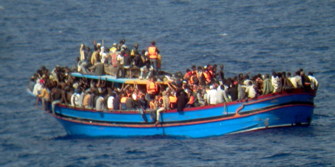 In this photo released by the Italian Navy on Monday, June 30, 2014, and taken on Sunday, June 29, 2014, a boat overcrowded with migrants is pictured in the Mediterranean Sea. The bodies of some 30 would-be migrants were found in in the hold of a packed smugglers' boat making its way to Italy, the Italian navy said Monday. The boat was carrying nearly 600 people, and the remaining 566 survivors were rescued by the navy frigate Grecale and were headed to the port at Pozzallo, on the southern tip of Sicily. (AP Photo/Italian Navy, ho)